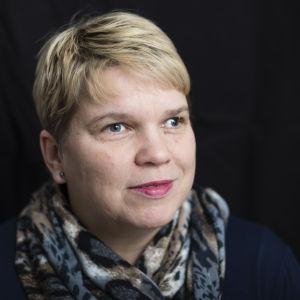 Kasvokuva Katja Kuuselasta mustaa taustaa vasten.