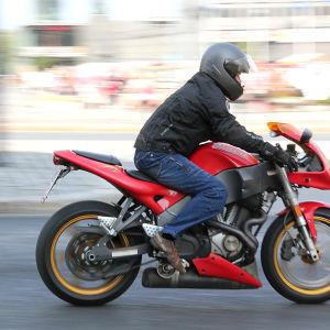 En människa som åker på en röd motorcykel. Personen är svarklädd med svart hjälm på huvudet.