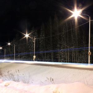Gatulyktor som lyser över vintrig landsväg i mörker.
