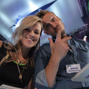 En kvinna och en man fotade underifrån, kvinnan ler och mannen visar fredstecken med fingrarna. Anna-Karin Siegfrids och Jontti Granbacka som programledare för MGP.