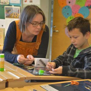 Maija Hurme hjälper en elev i Billnäs skola att skriva en egen bok.