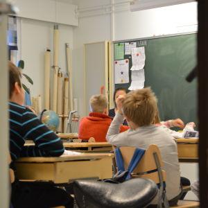 Barn sitter med ryggarna åt kameran i ett klassrum
