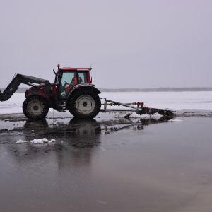 En traktor på Stadsfjärden i Vasa pumpar upp vatten på isen för att få den tjockare.