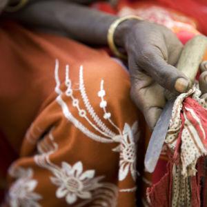 En kvinna håller en kniv som hon tidigare använde vid könsstympning i Etiopien.
