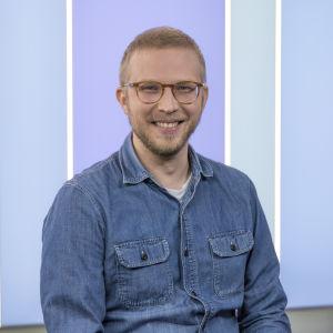Puoli seitsemän -ohjelman toimittaja Nuutti Takkinen poseeraa ohjelman studiossa