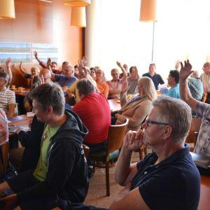 Deltagare i vindkraftverkmöte håller upp händerna.
