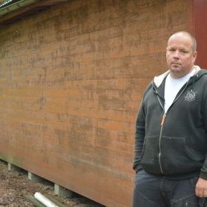 Patrik Wiksten invid den tomma väggen där veden brukar förvaras