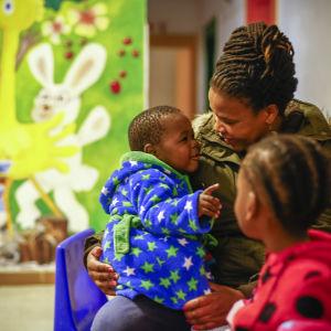 Två barn tillsammans med en vuxen på barnhemmet HOKISA, som sköter om barn påverkade eller smittade av hiv.
