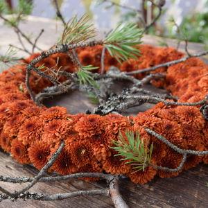 En krans av oranga blommor och tallkvistar