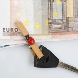 En klädnypa som håller i en nyckel och en bunt sedlar.