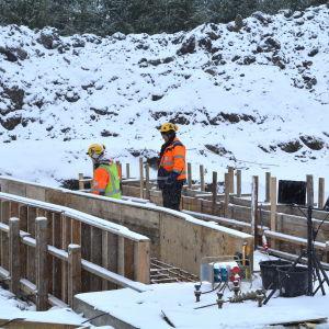 byggarbetare jobbar ut i vit vinter