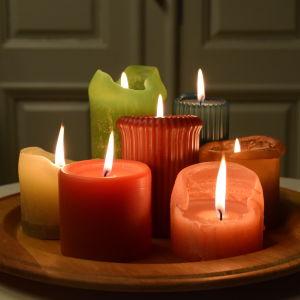 Sju brinnande ljus i olika färger på en bricka.
