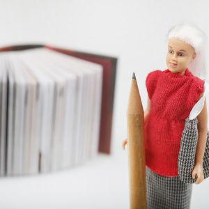 En kvinna håller i en penna, i bakgrunden en bok.