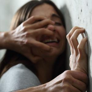 En man tycker ner en kvinna mot marken.