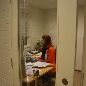 Kvinna sitter i ett arbetsrum och jobbar på dator.