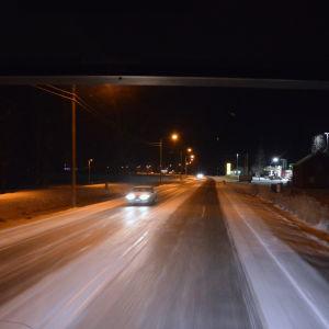 Halt på vägen. Bilens strålkastare speglas på den hala vägytan.