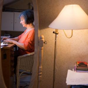 Henkilö kirjoittaa tietokoneella työpöydän ääressä.