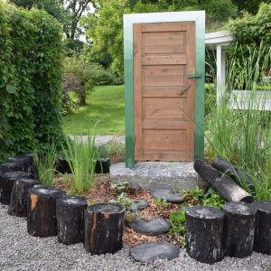 Trädgårdsrabatt med sumpmarksväxter och en fristående dörr i mitten