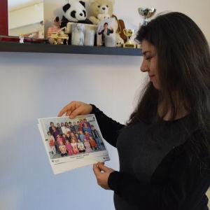 kvinna håller i ett fotografi