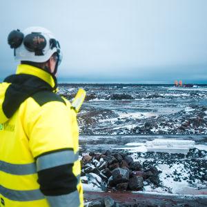 En man i arbetskläder och hjälm tittar ut över det kala området i Hanhikivi där kärnkraftverket ska byggas.