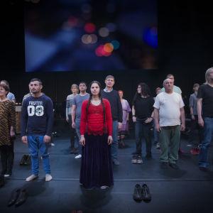 romska deltagare samt andra amatörer och proffs står på Folkoperans scen, tittar rakt fram, har tagit av sig skorna.