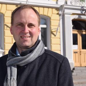 En man i halsduk och jacka står utanför stadshuset i Ekenäs. Raseborgs stadsdirektör Tom Simola.