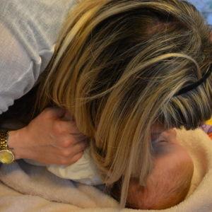 En mor böjer sig över sitt spädbarn.