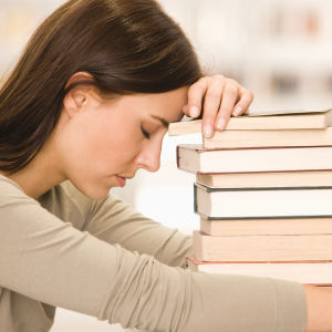 Kvinna lutar sig trött mot en trave böcker.