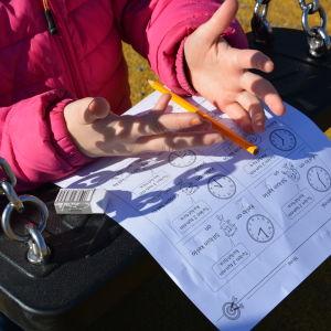 Barn arbetar med papper och penna med gunga som underlag.