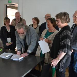 Flera personer samlade för att skriva under ett papper.