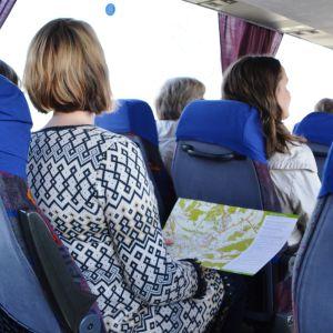 Personer sitter i buss med karta i handen.