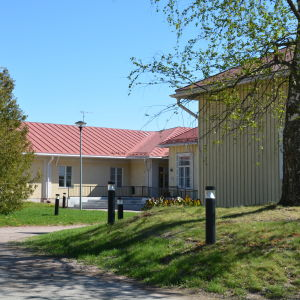 Byggnad med gräs och träd i förgrunden.
