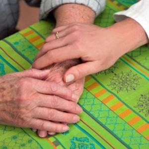 Yngre hand på två rynkiga, äldre händer på bordet.