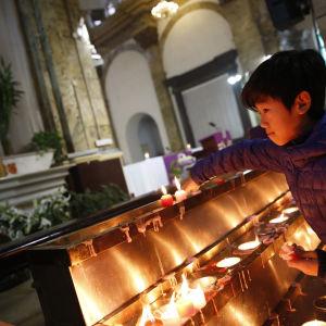 En pojke tänder ett ljus i en katolsk kyrka i Peking.