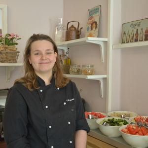 Hanna Brofelt står i svart kockjacka bredvid salladsskålar.