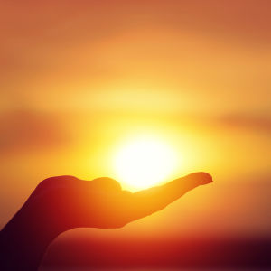 silhouette of a hand holding the sun