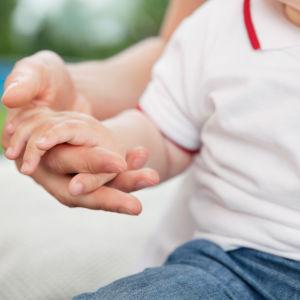Ett litet barn håller sin förälder i handen.