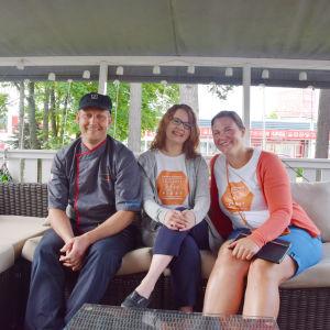 Tre personer sitter i en soffa på en terass och ler. En man och tre kvinnor. I bakgrunden träd