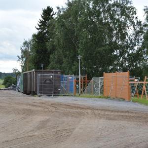På halva bilden ser man byggstaket och containrar. På andra halvan ser man gräsmatta och klätterställningar, bollplank och gungor.