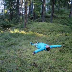 Nainen makaa metsässä