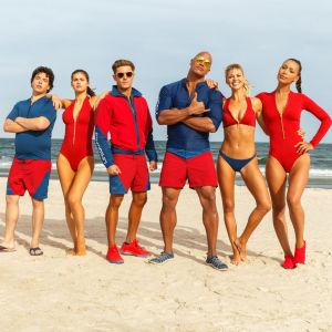 Baywatch livräddningsteam med Mitch (Dwayne Johnson) i spetsen poserar på stranden.