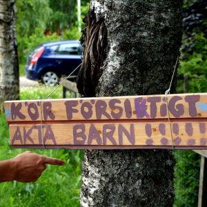 Hemmasnickrad vägskylt hänger på ett träd.