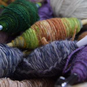 Garnnystan på spolar i en hög, lila, gröna och gråa.