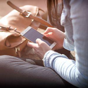 En ung flicka sitter på marken med benen i kors och en mobiltelefon i handen.
