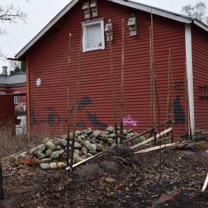 En halvfärdig gärdesgård bredvid ett rött uthus.
