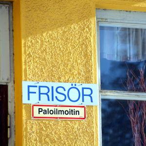Frisörskylt uppsatt på en gul vägg.