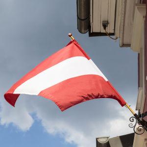 Itävallan lippu liehuu talon seinässä.