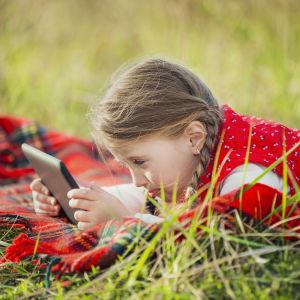 En flicka ligger på en gräsmatta på en filt och spelar på en I-Pad.