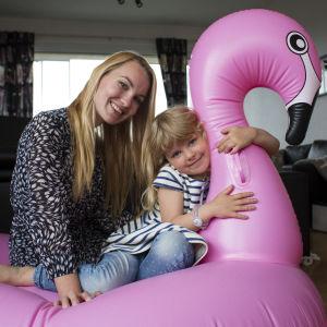Mamma Ellen och dottern Wilda sitter på en uppblåsbar rosa flamingo i deras vardagsrum.