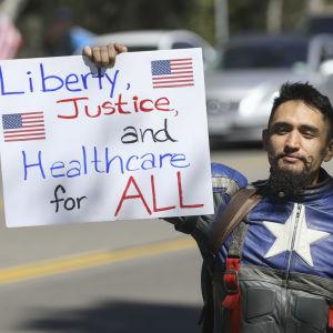 En demonstrant håller upp ett plakat med krav på vård för alla amerikaner.